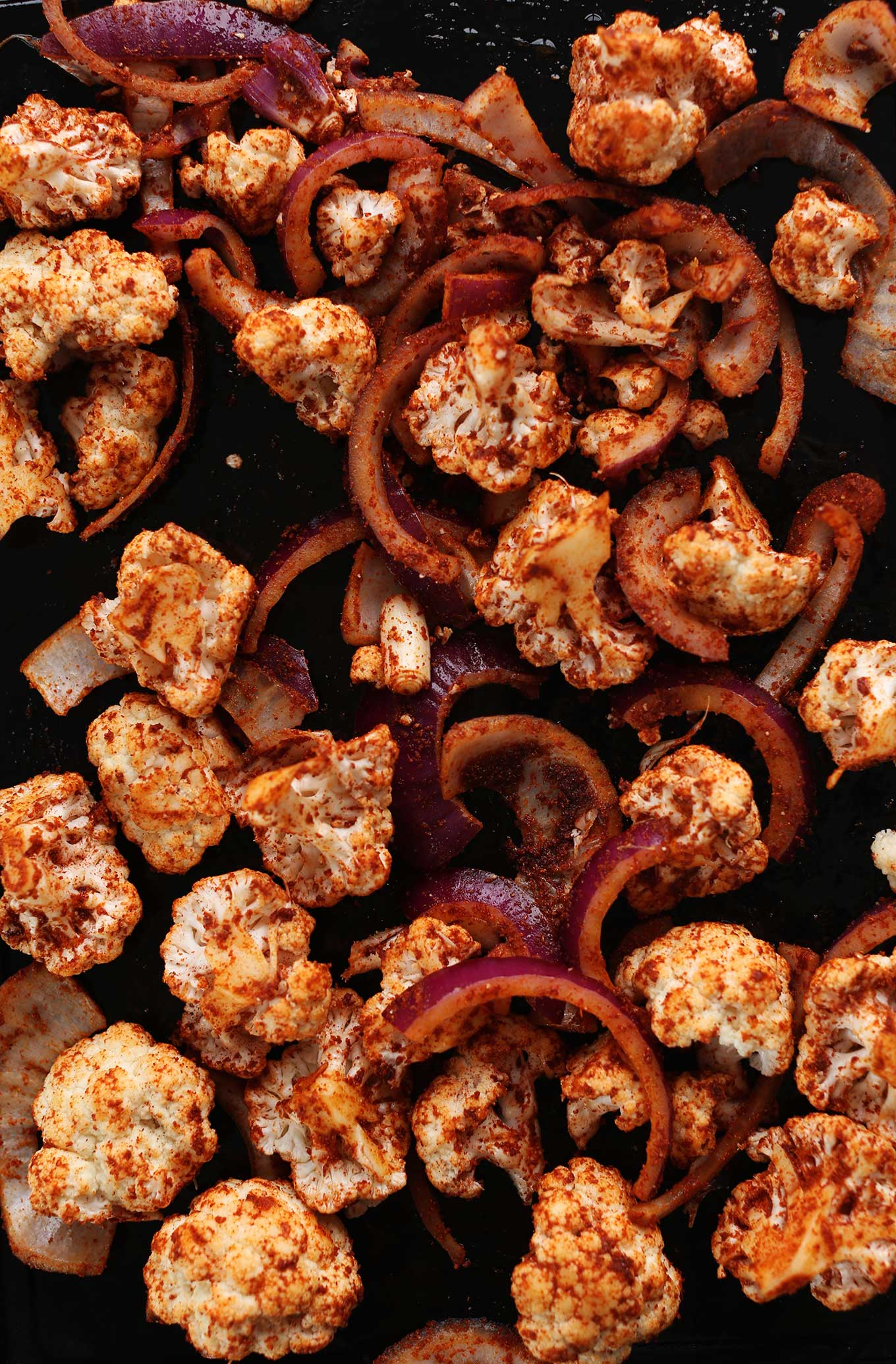 Baking sheet filled with cauliflower and red onions coated in masala spice blend