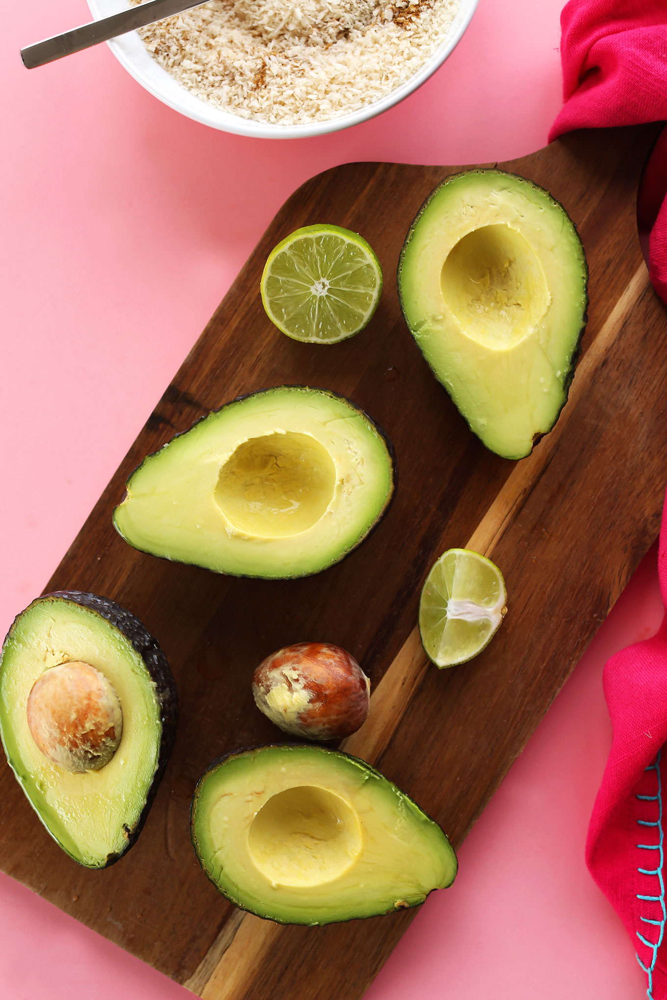 Cutting board with halved avocados and limes