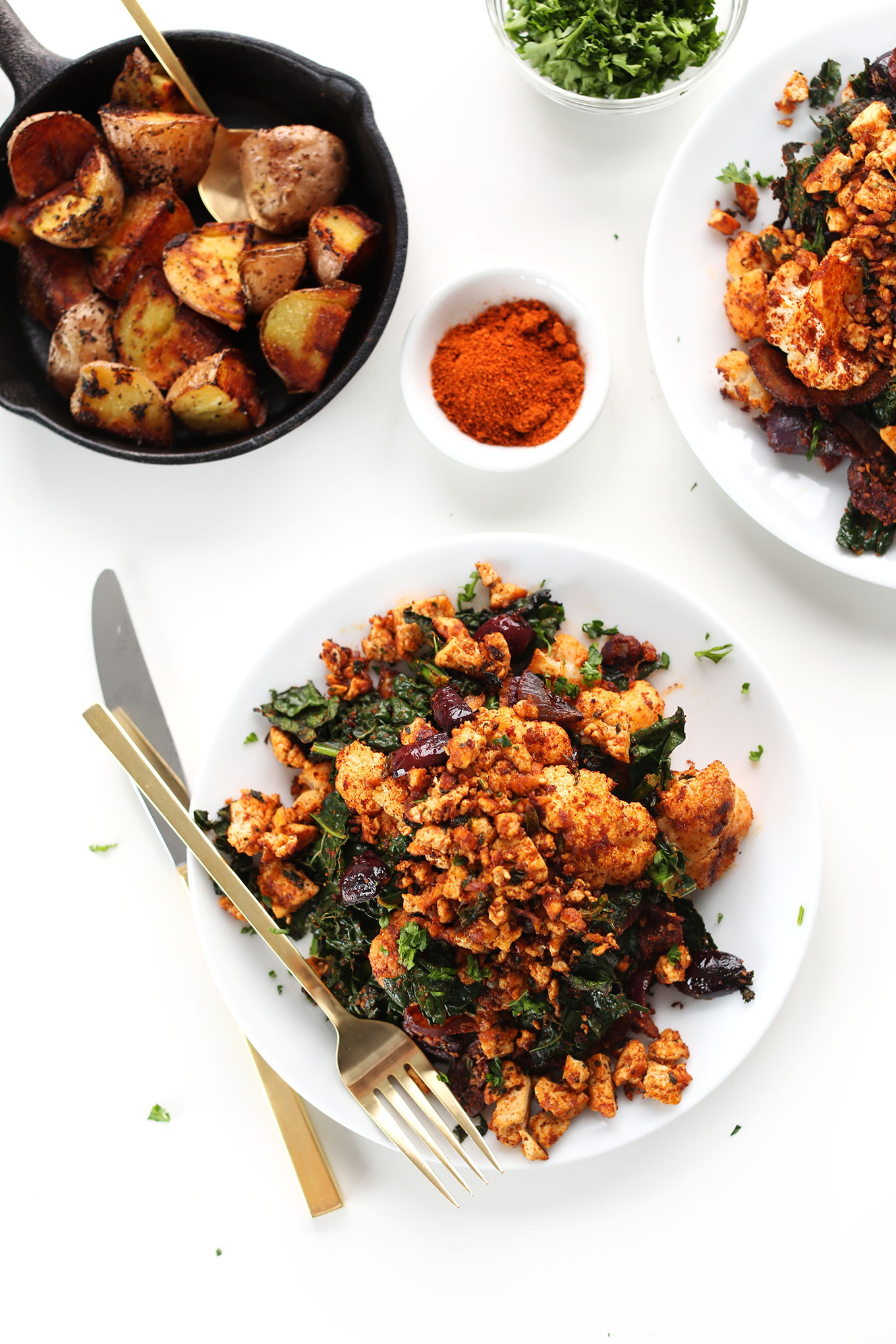 Plates of our Tofu Scramble recipe with Masala-spiced cauliflower, kale, onion, and potatoes