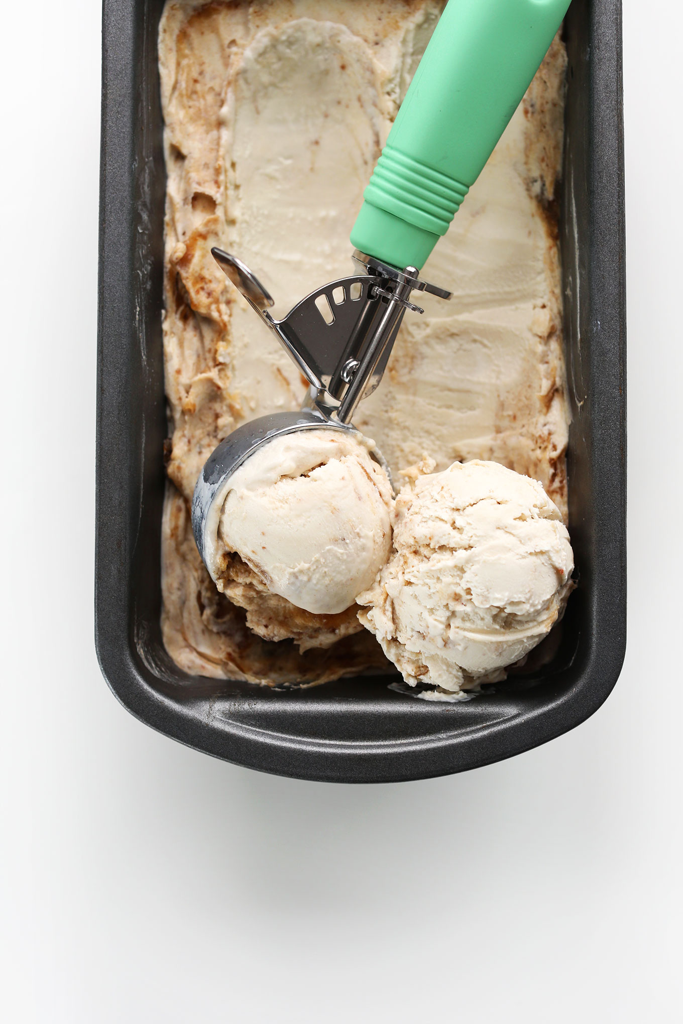Using an ice cream scooper to grab scoops of creamy Vegan Coconut Caramel Sea Salt Ice Cream