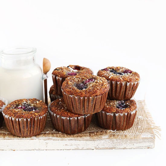 Batch of homemade Gluten-Free Coconut Berry Muffins on a wood board with a jar of dairy-free milk