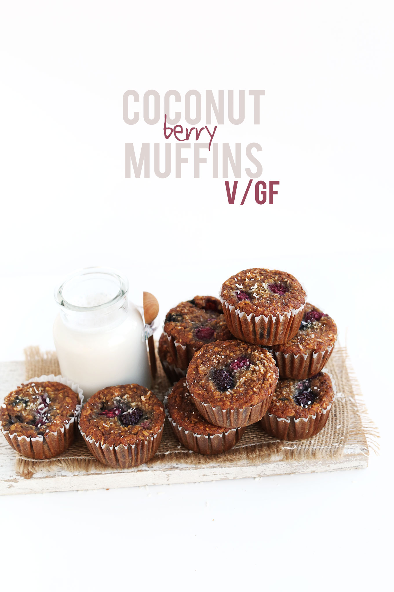 Wood cutting board with a batch of our Coconut Berry Muffins and a glass of almond milk