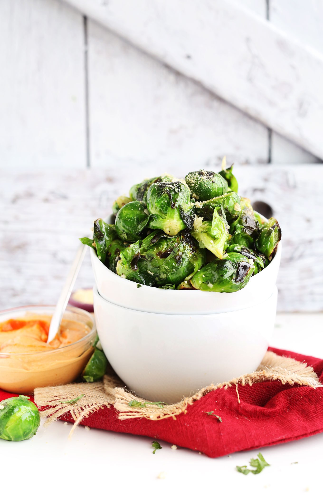 Bowl of Crispy Roasted Brussel Sprouts with a smaller bowl of spicy Sriracha Aioli