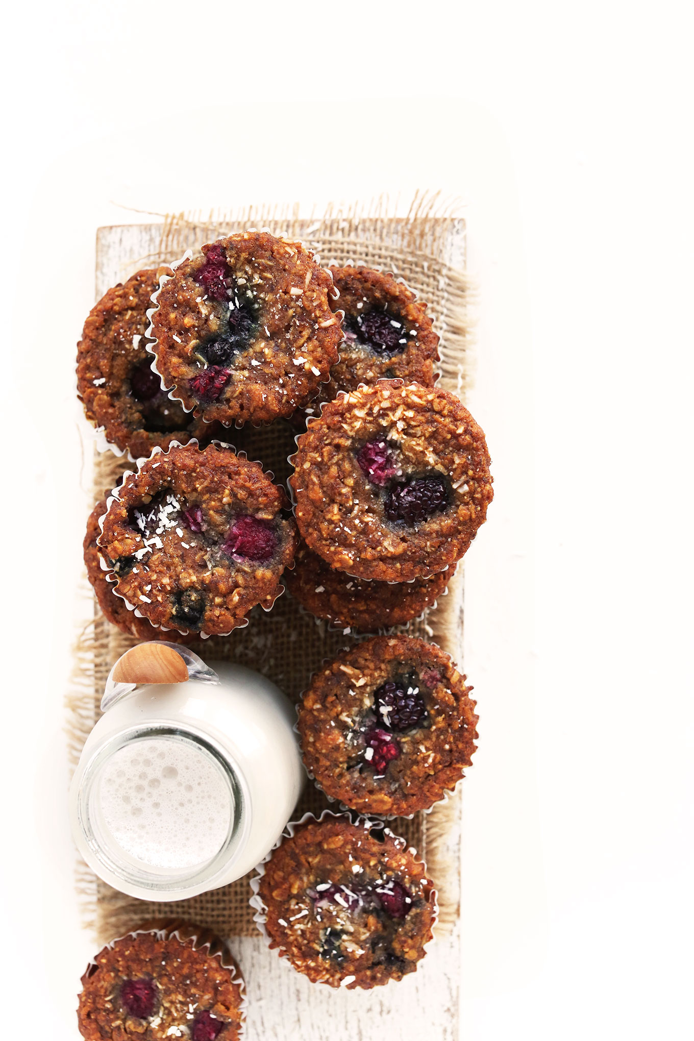 Batch of our simple Vegan Berry Coconut Muffins recipe on a wood board with nut milk