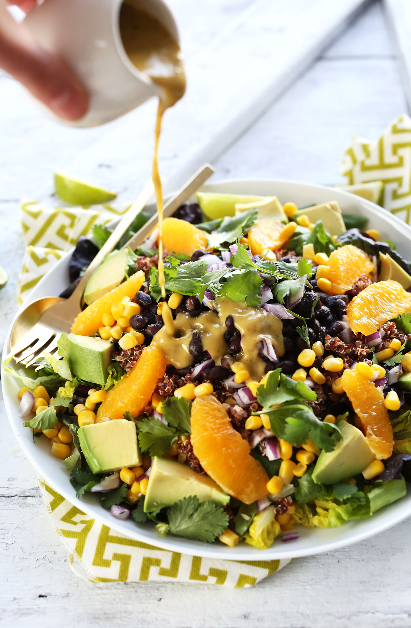 Drizzling Creamy Orange Chili Dressing onto Vegan Mexican Quinoa Salad