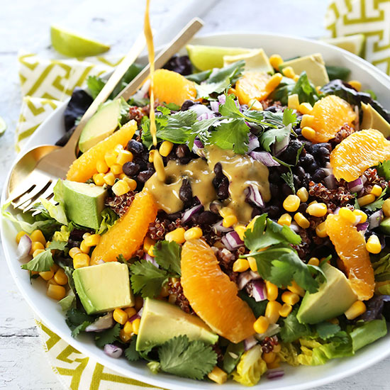 Pouring Creamy Orange Chili Dressing onto a bowl of Vegan Mexican Quinoa Salad