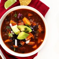 Bowl of Sweet Potato Black Bean Chili topped with diced avocado and cilantro
