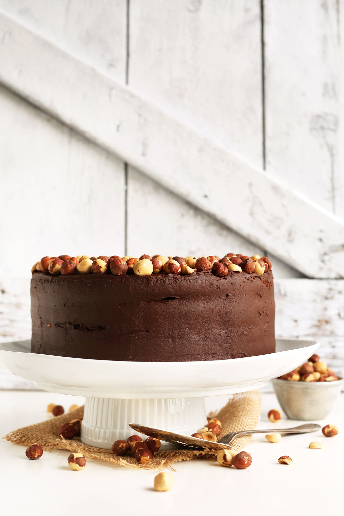 Vegan GF Chocolate Hazelnut Cake perched on a cake stand