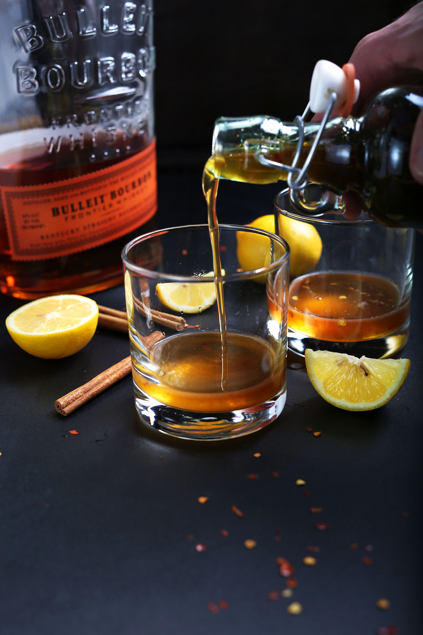 Pouring Chili-Infused Maple Simple Syrup into a glass to make Cinnamon Bourbon Hot Toddys