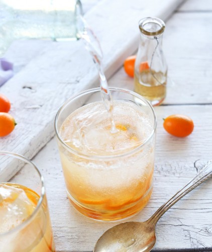 Pouring sparkling water into a glass to make our All Natural Citrus Gin and Tonics recipe
