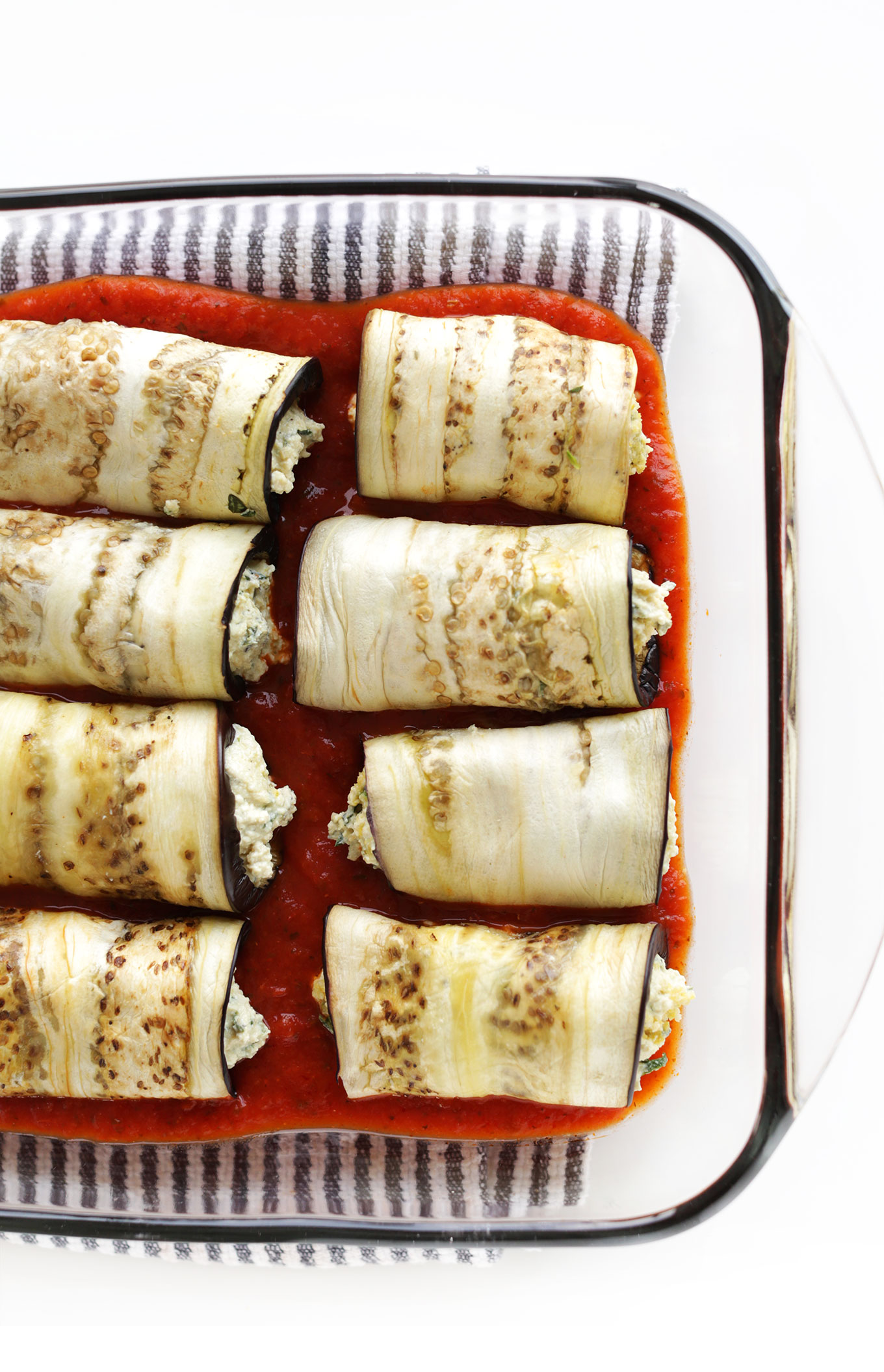 Baking pan with vegan Eggplant Lasagna Roll-Ups resting in marinara sauce