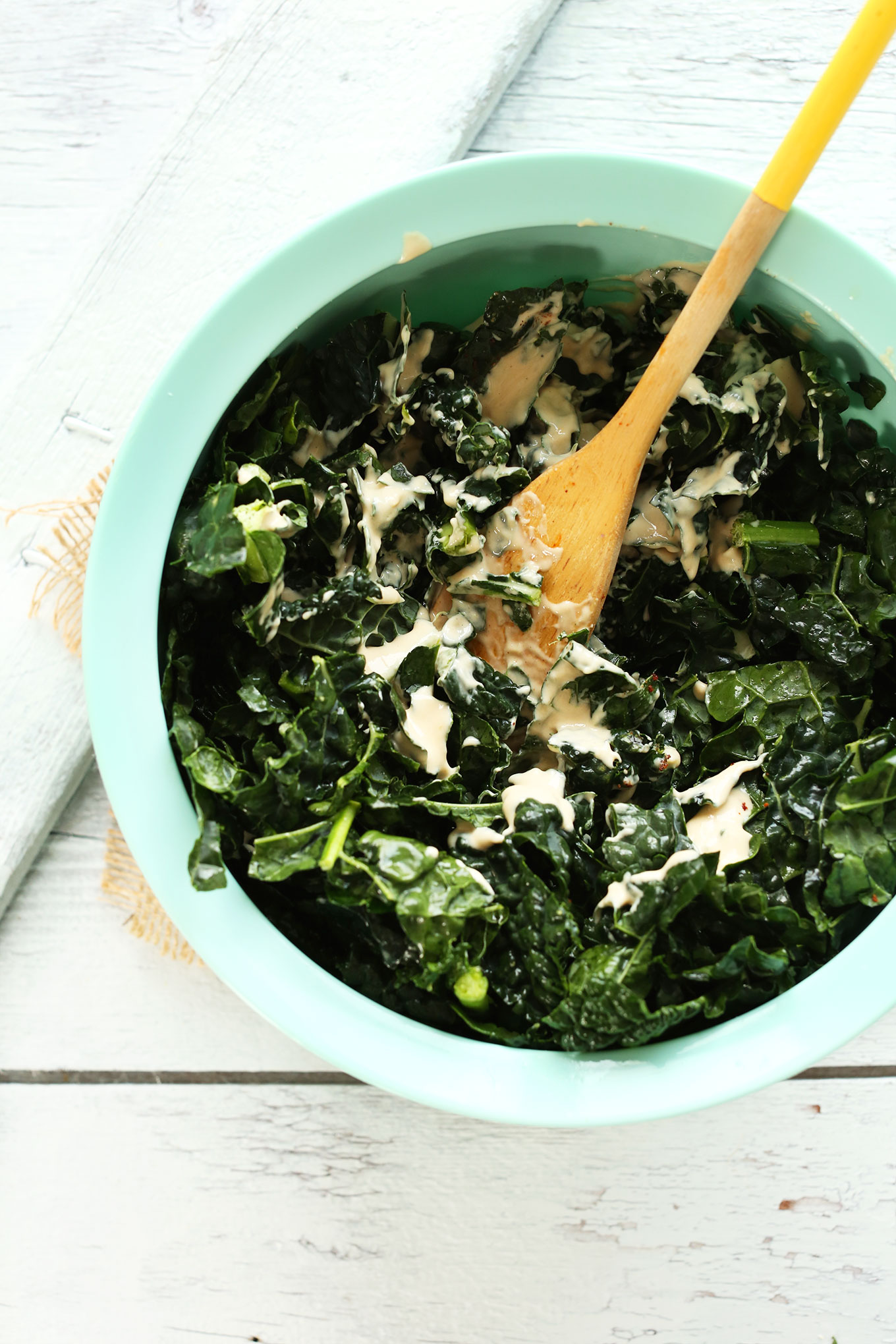 Mixing kale with dressing in a large mixing bowl