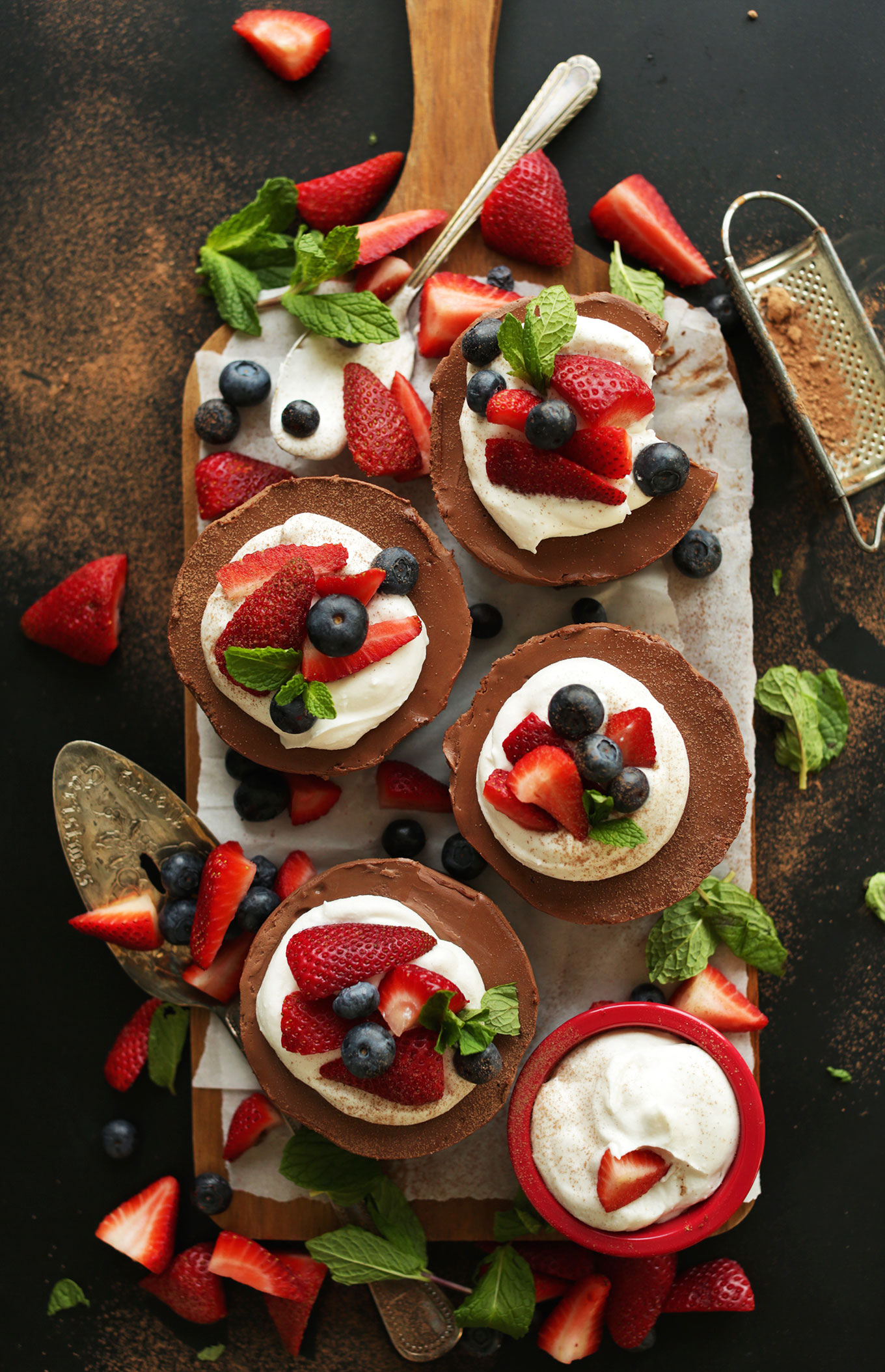 Top view of a batch of our mini Vegan Chocolate Cheesecakes topped with coconut whip and fresh berries