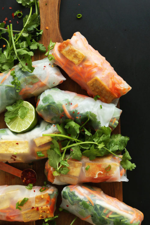 Wood cutting board with gluten-free vegan Bahn Mi Spring Rolls, dipping sauce, fresh cilantro, and lime