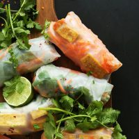 Several Banh Mi Spring Rolls on a cutting board with lime and fresh cilantro