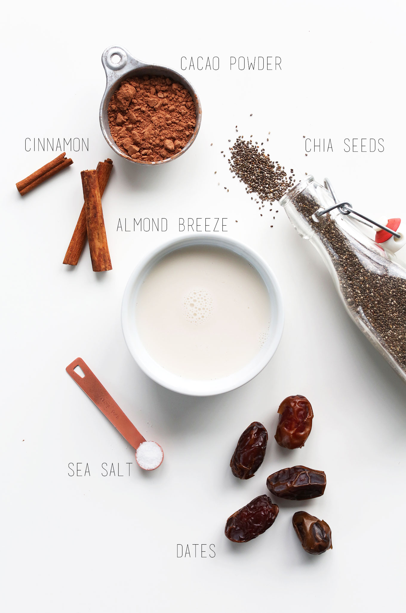 Cacao powder, cinnamon, almond milk, sea salt, dates, and chia seeds for making Chia Pudding