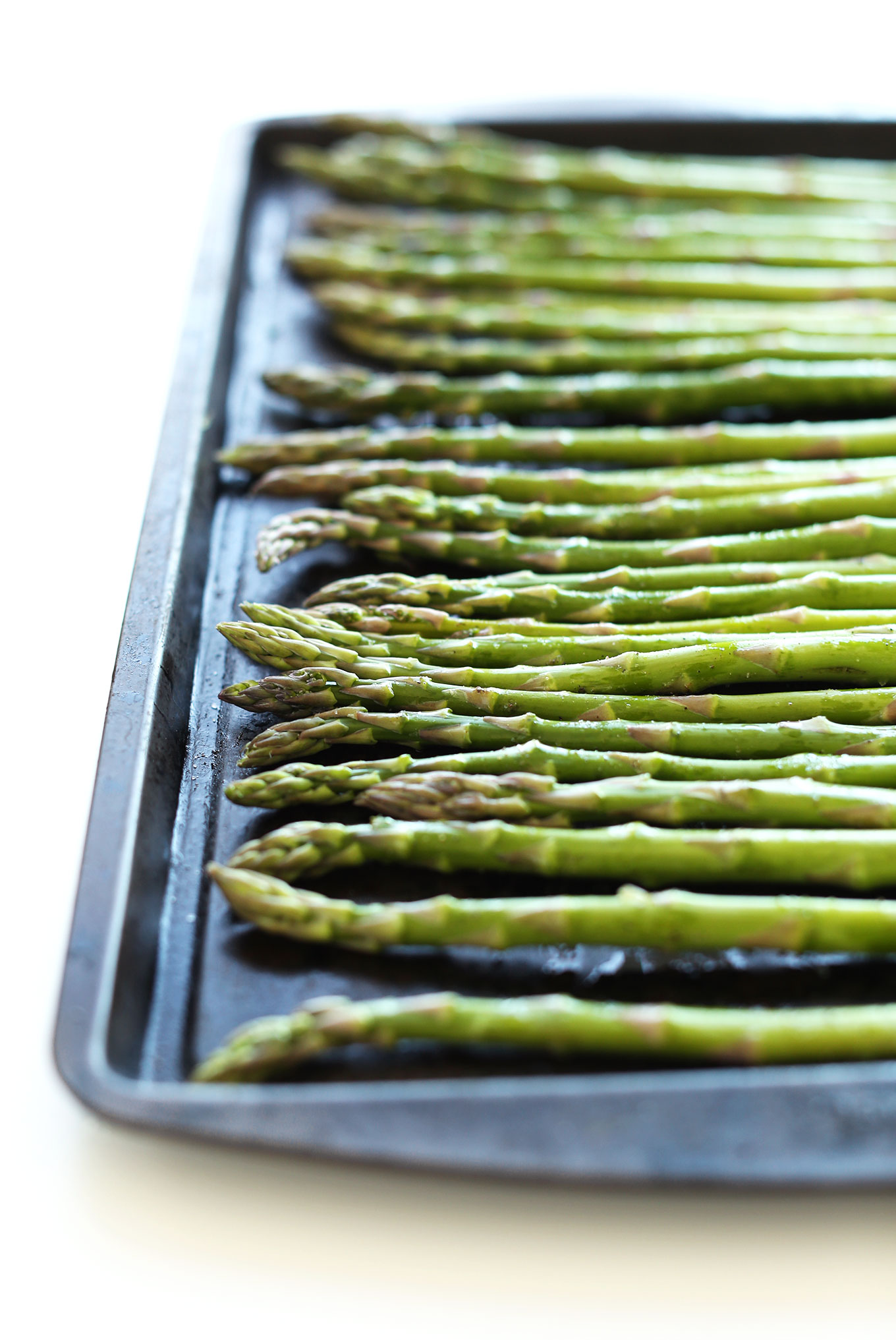 Asparagus spears on a baking sheet for making Creamy Asparagus and Pea Soup