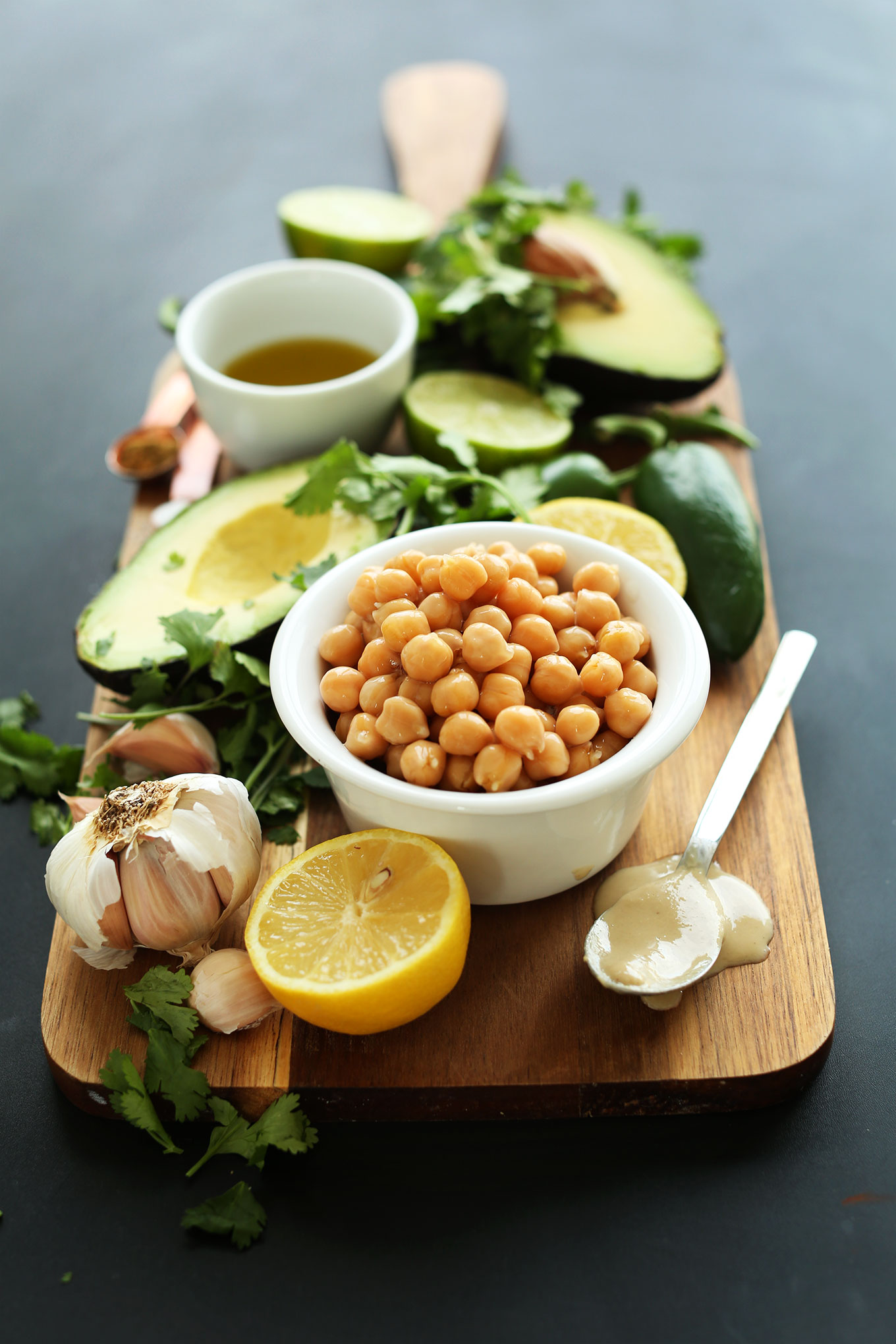 Wood board with chickpeas and other ingredients for making homemade Creamy Roasted Jalapeno Hummus