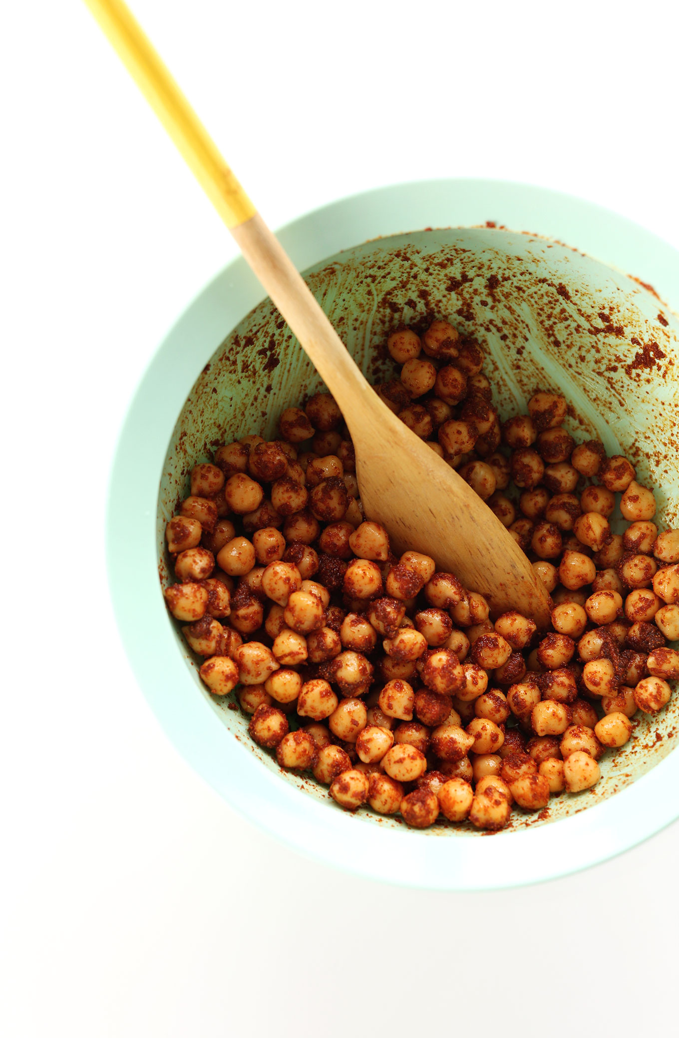 Mixing bowl with spices and chickpeas for adding protein to our vegan salad