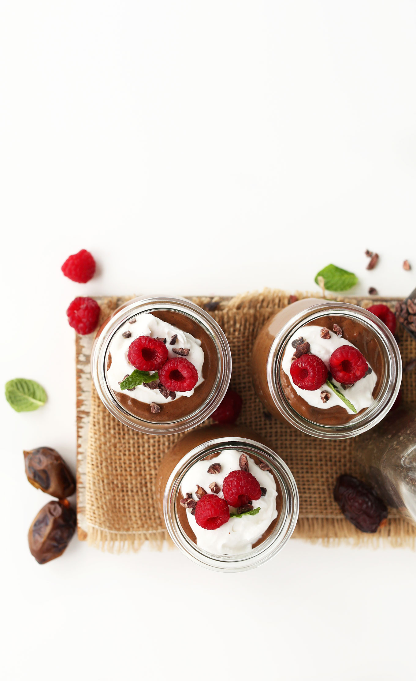 Top view showing jars of vegan Chocolate Chia Seed Pudding topped with coconut whip and raspberries
