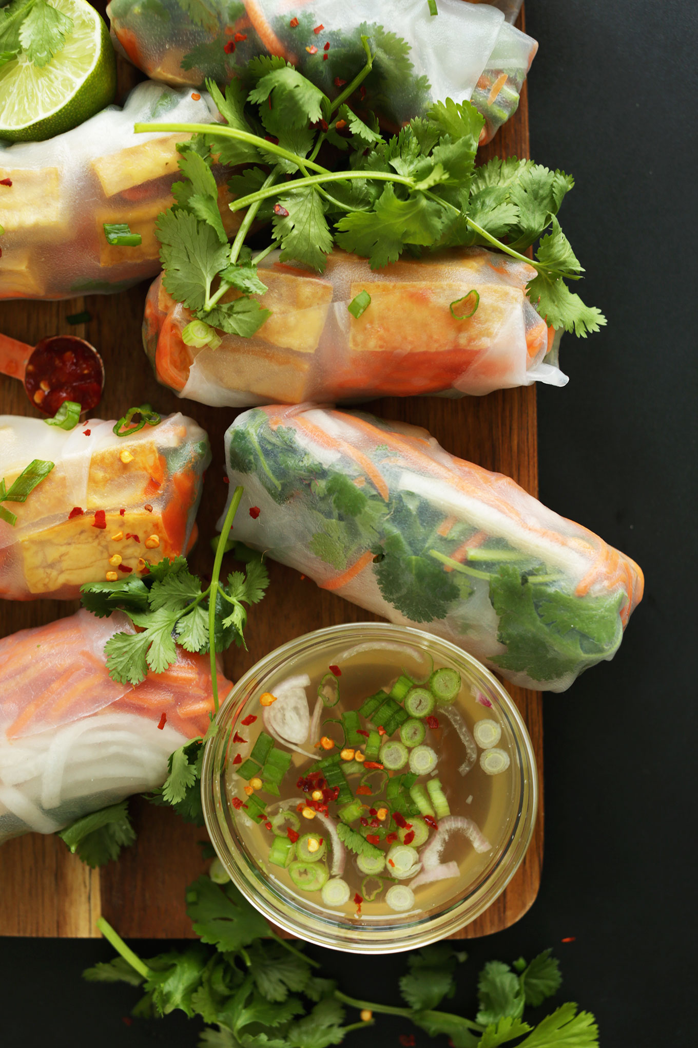 Wood platter of Bahn Mi Spring Rolls and sauce for a fresh vegan meal