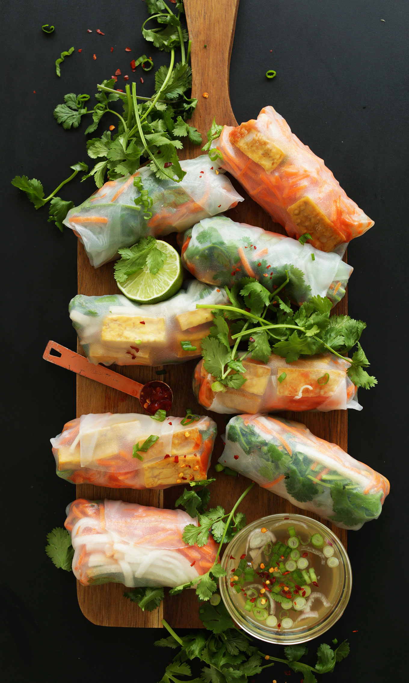 Wood cutting board with fresh and satisfying Bahn Mi Spring Rolls