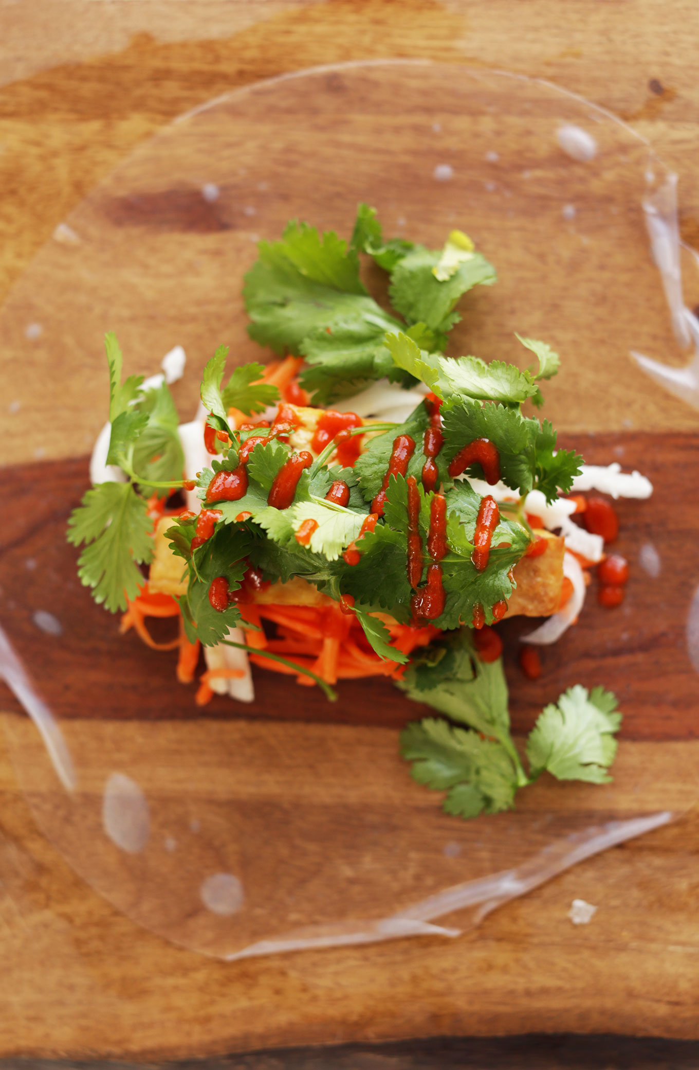 Wood cutting board with a rice paper wrapper and fillings for vegan Bahn Mi Spring Rolls