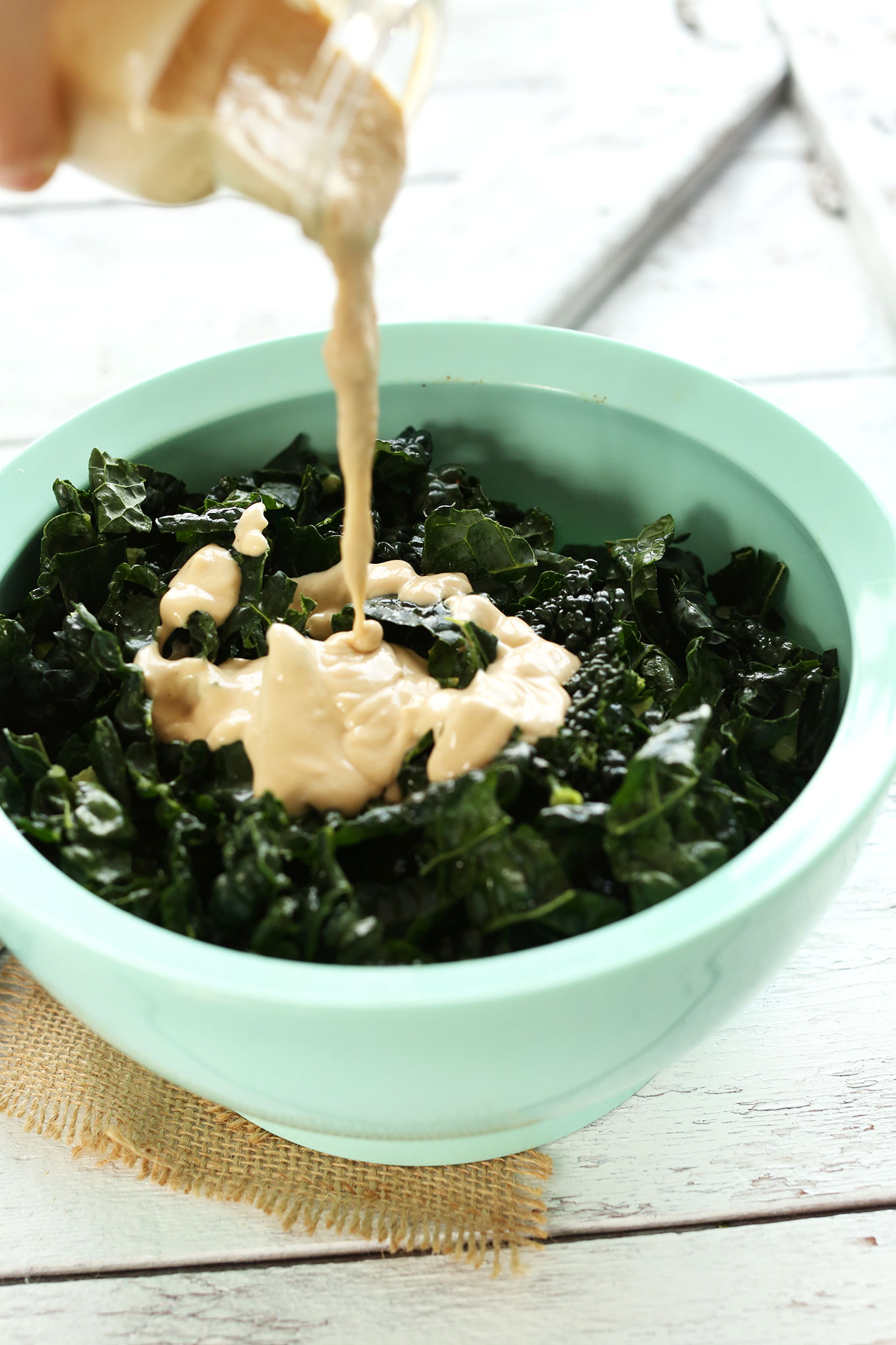 Pouring dressing onto our Garlicky Kale Salad recipe
