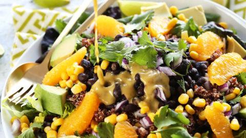 Pouring a delicious homemade vegan dressing onto Mexican Quinoa Salad