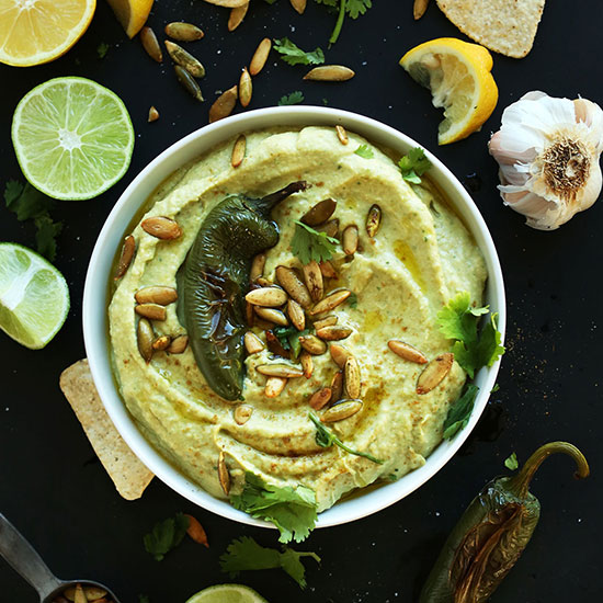 Bowl of homemade Jalapeno Hummus topped with a roasted jalapeno and pumpkin seeds