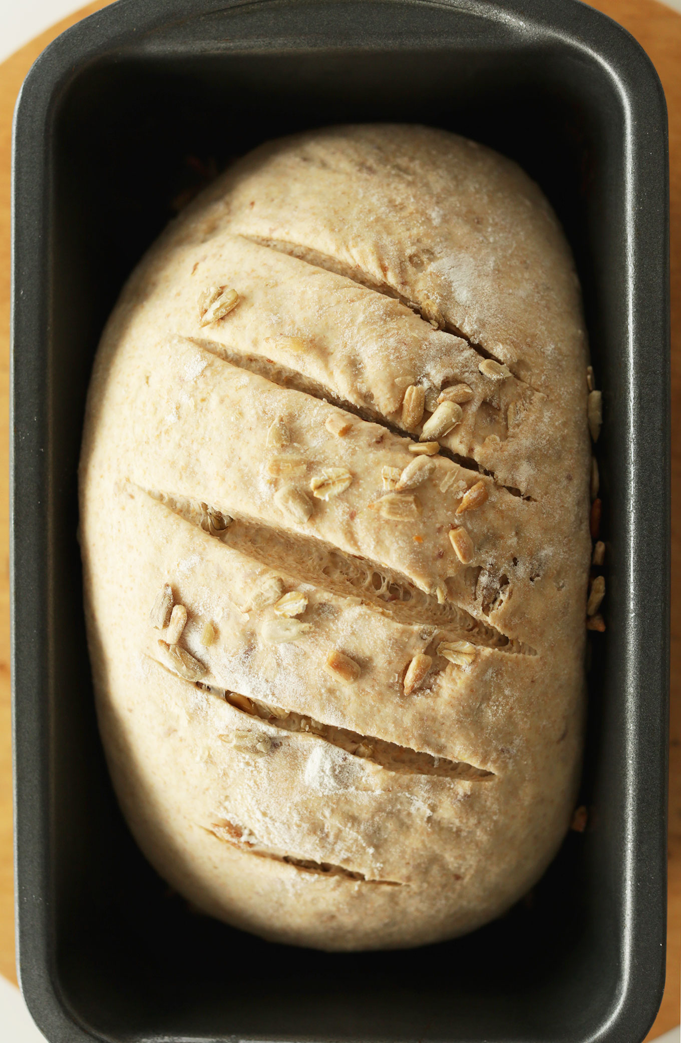 Freshly baked loaf of Whole Grain Seedy Vegan Bread in a bread pan