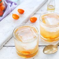 Kumquats and ice cubes in glasses filled with our homemade Gin and Tonic recipe