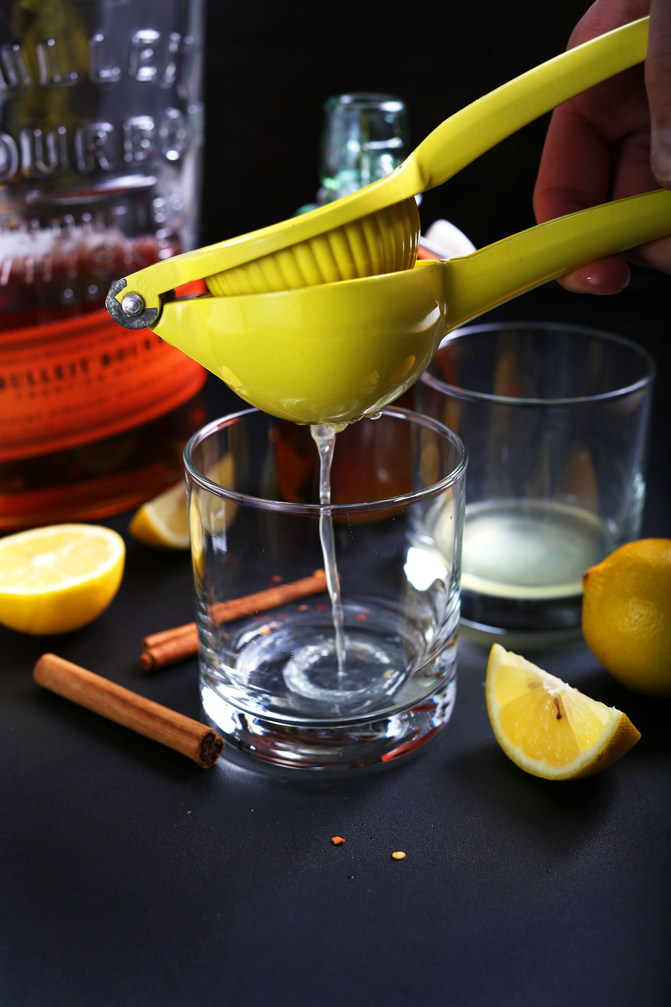Squeezing lemon juice into glasses to make the ultimate homemade Hot Toddy