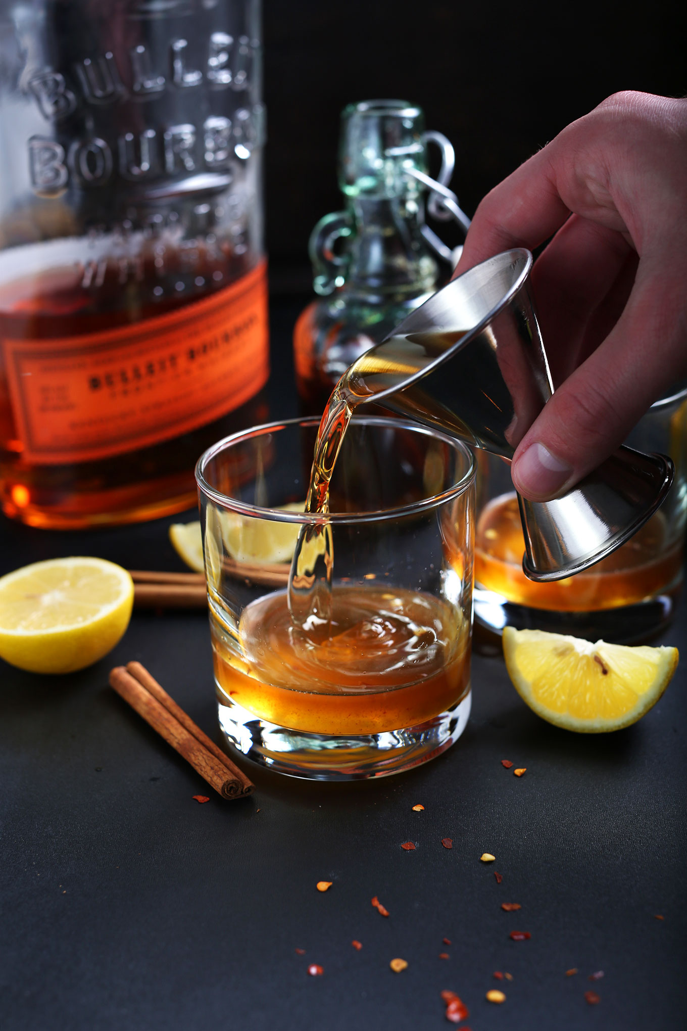Pouring bourbon into a glass for making a homemade naturally-sweetened Hot Toddy
