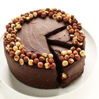 Partially sliced plate of Vegan GF Chocolate Hazelnut Cake