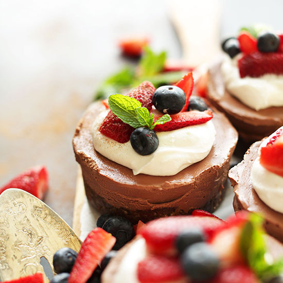 Platter of Mini Vegan No-Bake Chocolate Cheesecakes topped with fresh berries