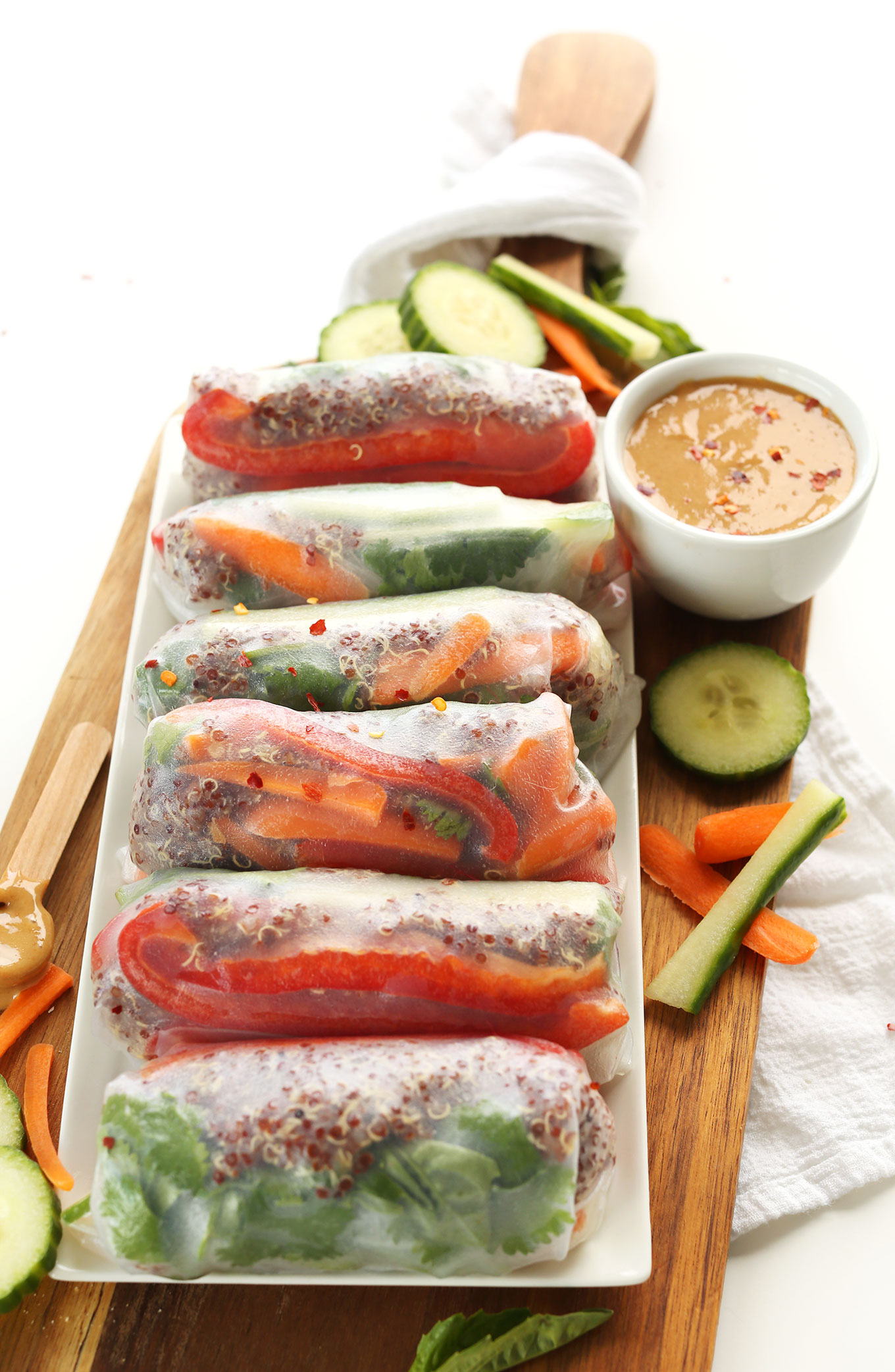 Platter of gluten-free vegan Quinoa Spring Rolls with a bowl of Cashew Dipping Sauce