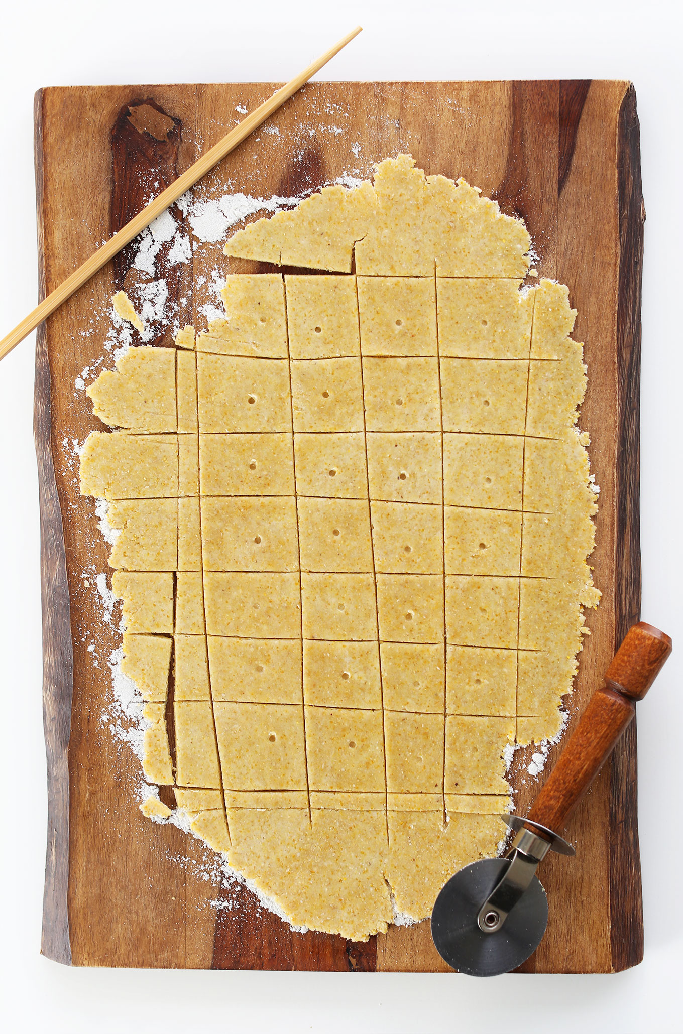 Using a pizza cutter and chopstick to make cuts and dots in our homemade Peanut Butter Cheese Crackers recipe