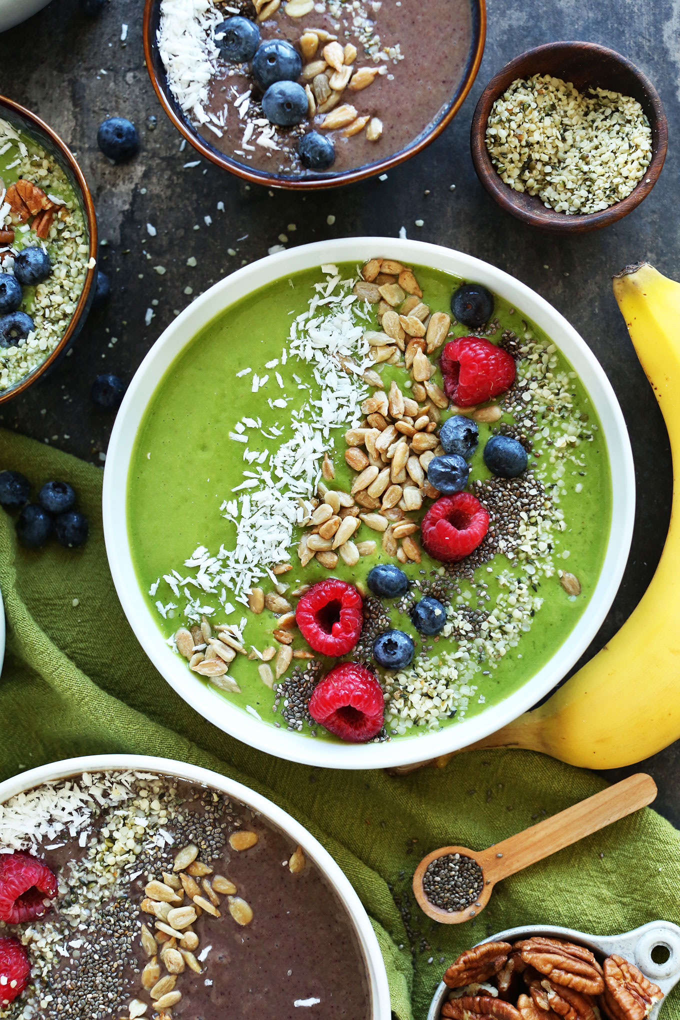 Super Green Smoothie Bowl topped with shredded coconut, sunflower seeds, hemp seeds, chia seeds, and fresh berries