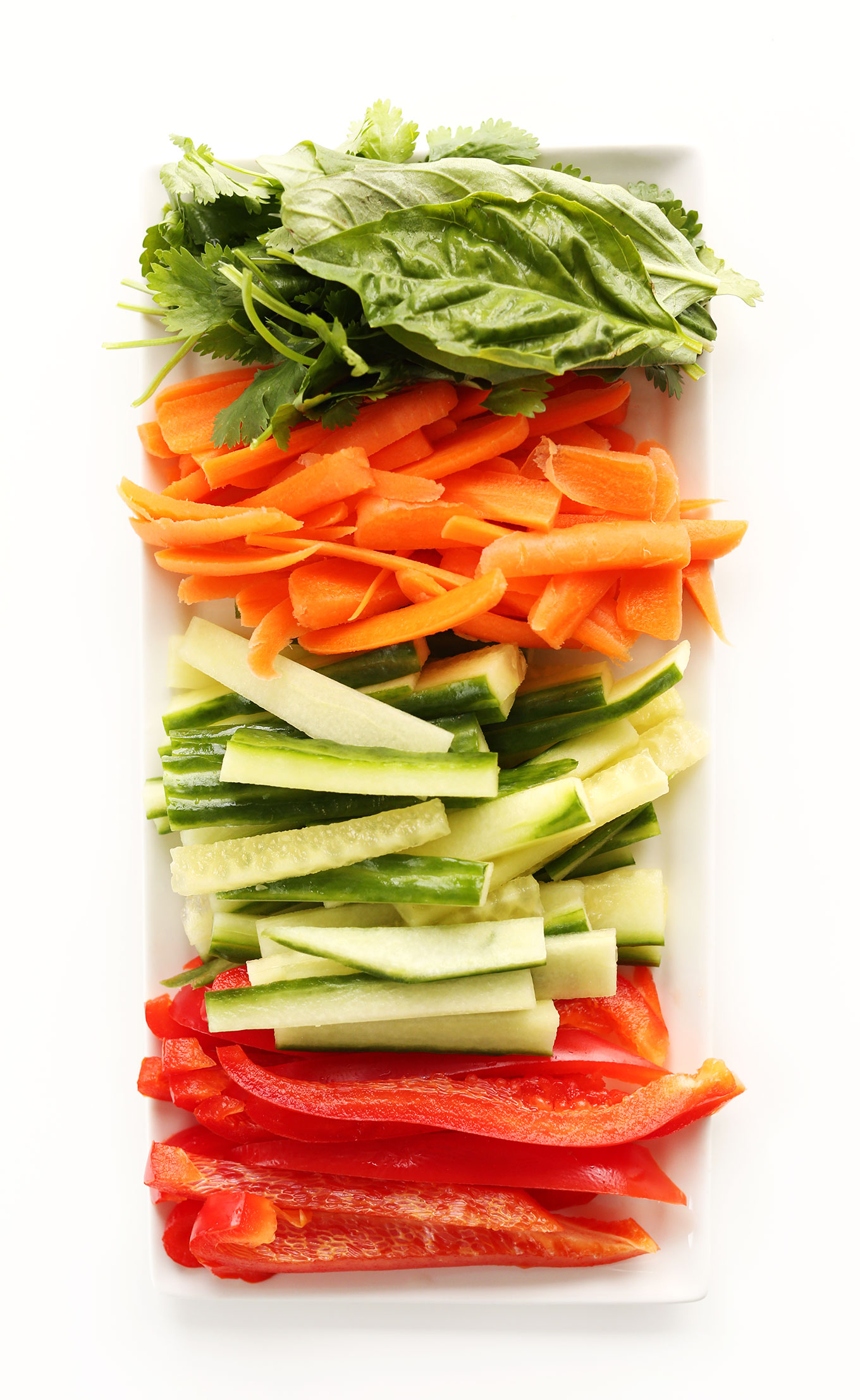 Platter of fresh basil, carrots, cucumber, and red bell pepper for making healthy Quinoa Spring Rolls