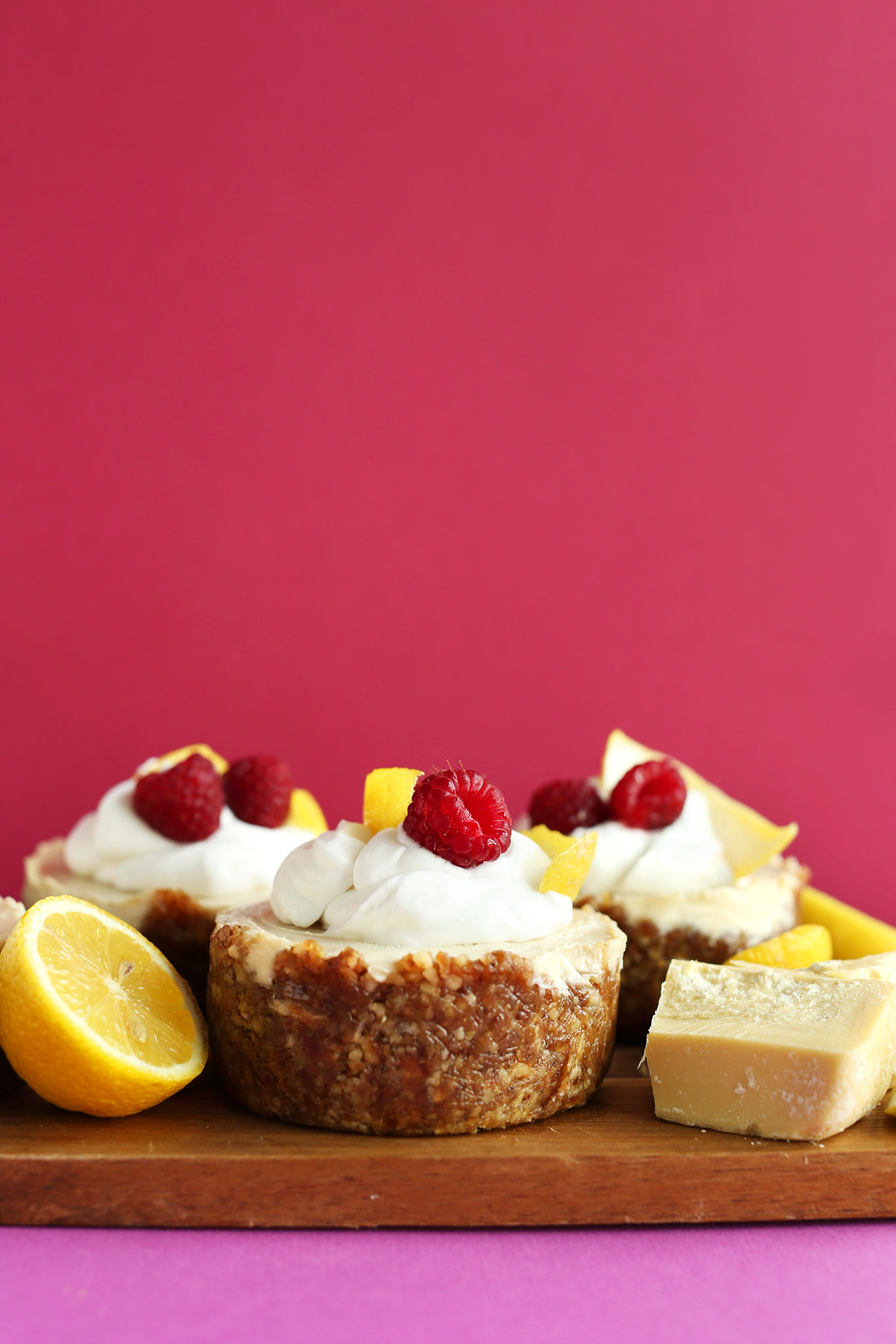 Wood board with mini vegan Lemon White Chocolate Cheesecakes with Walnut-Date Crust