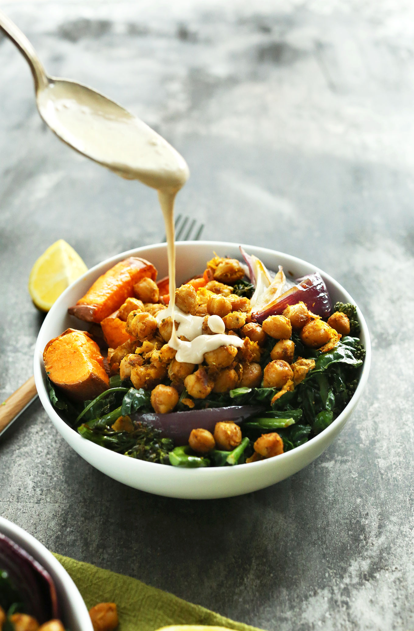 Pouring Tahini Maple Sauce onto a gluten-free vegan Sweet Potato Chickpea Buddha Bowl