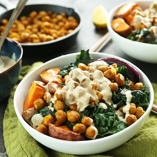 Healthy Sweet Potato Chickpea Buddha Bowls beside a bowl of tahini sauce and skillet of chickpeas