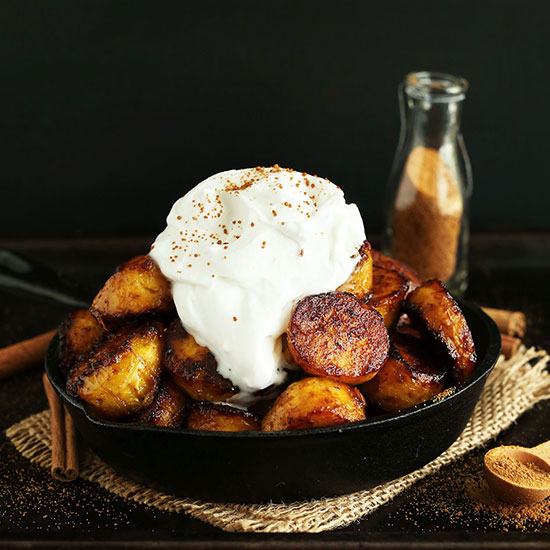 Skillet piled high with Coconut Sugar Caramelized Plantains and coconut whipped cream