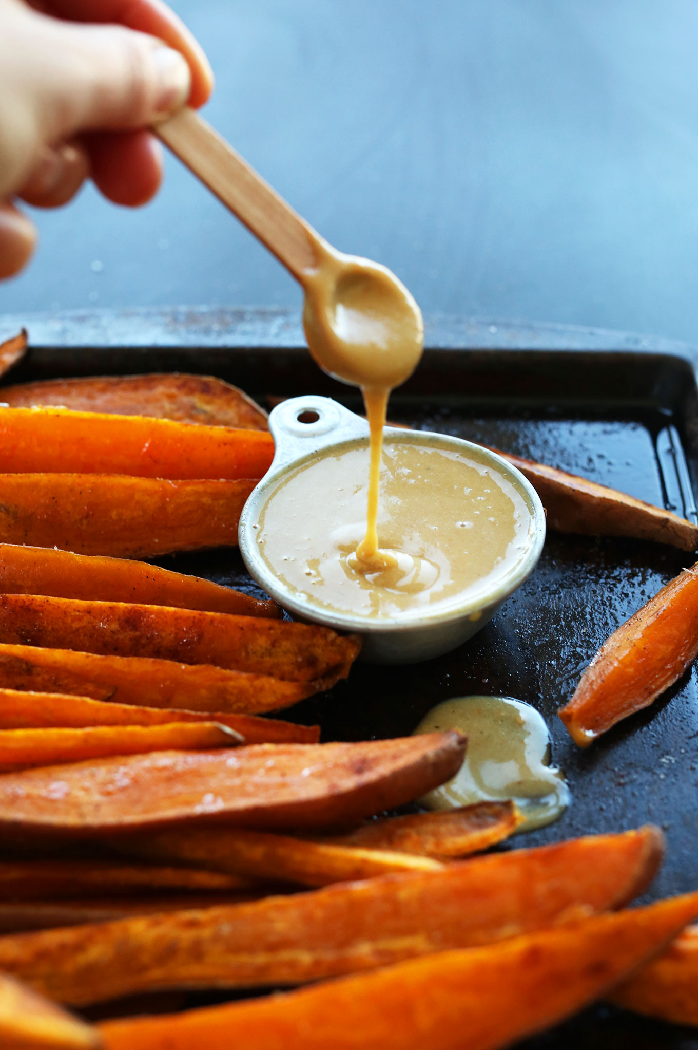 Using a small spoon to drizzle No-Honey Mustard Dipping Sauce for a gluten-free vegan snack