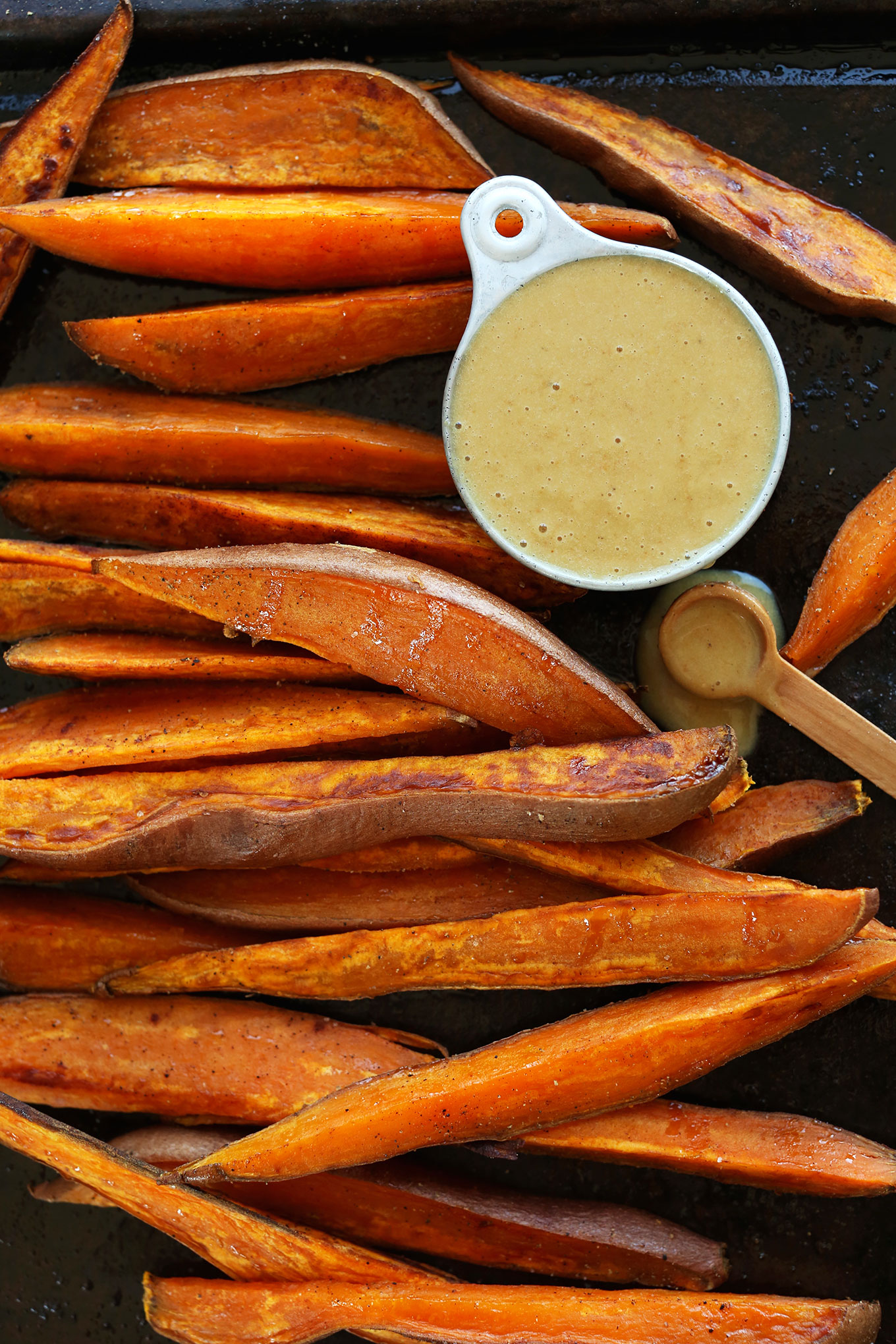 Perfectly browned Savory Sweet Potato Wedges with a side of vegan No-Honey Mustard Dipping Sauce