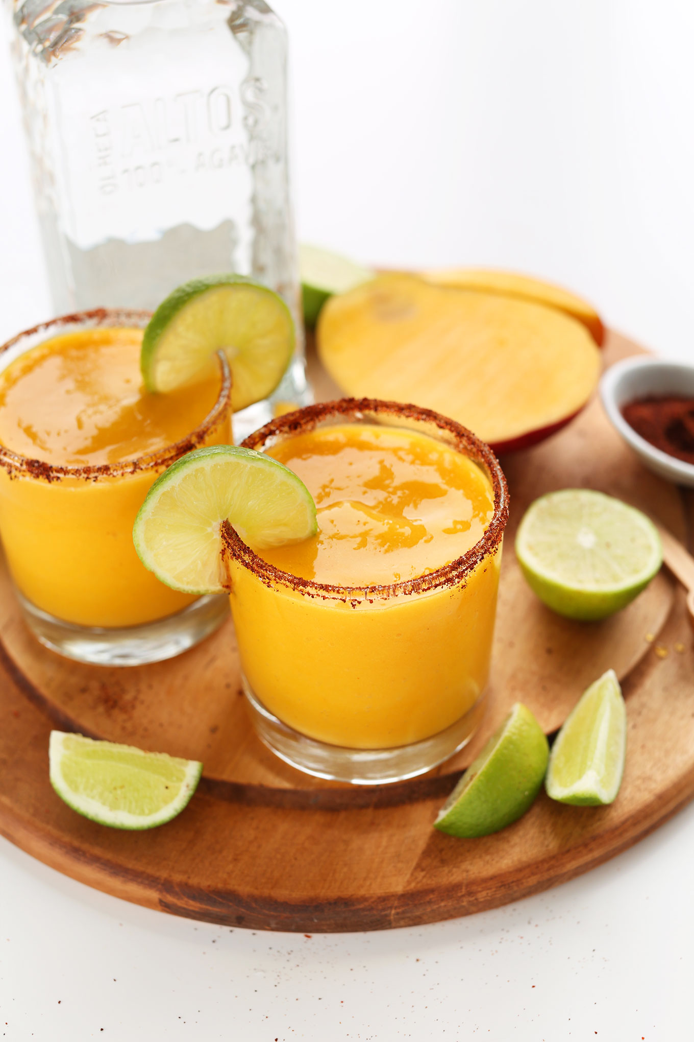 Perfectly sweet, tart, and spicy Blended Mango Chili Margaritas on a cutting board with fresh limes