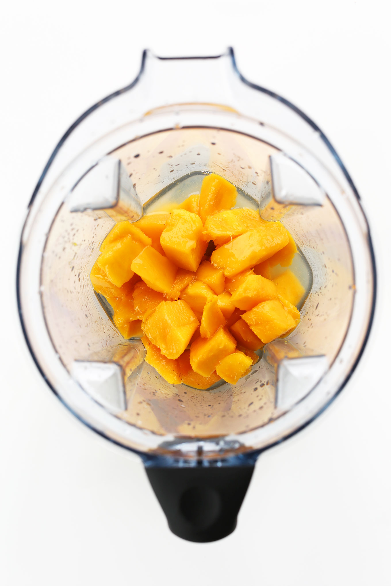 Blender filled with ingredients for making easy blended mango margaritas