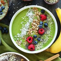 Vibrant Green Smoothie Bowl topped with shredded coconut, sunflower seeds, berries, chia seeds, and hemp seeds
