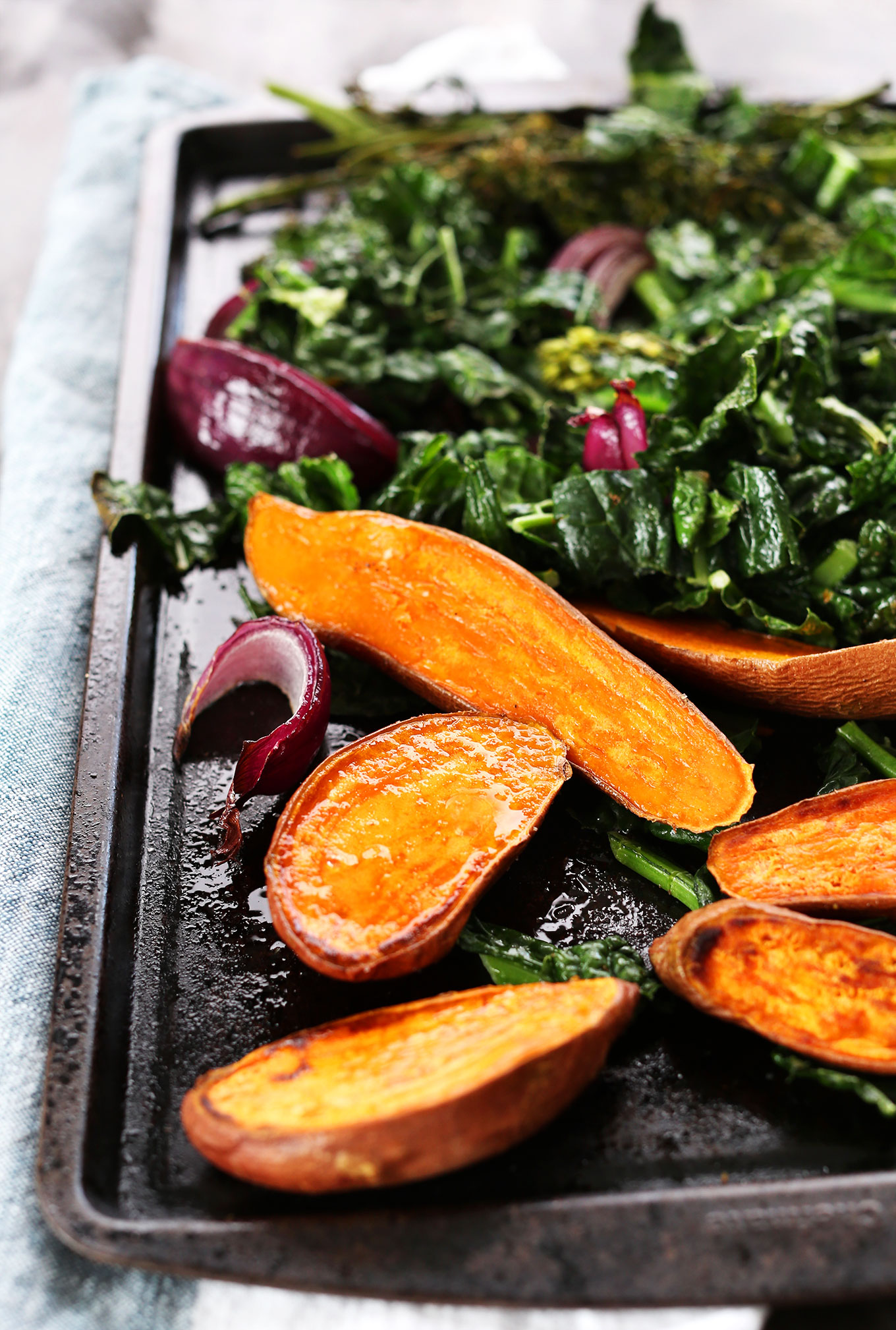 Baking sheet with sweet potatoes and greens for making vegan Buddha Bowls
